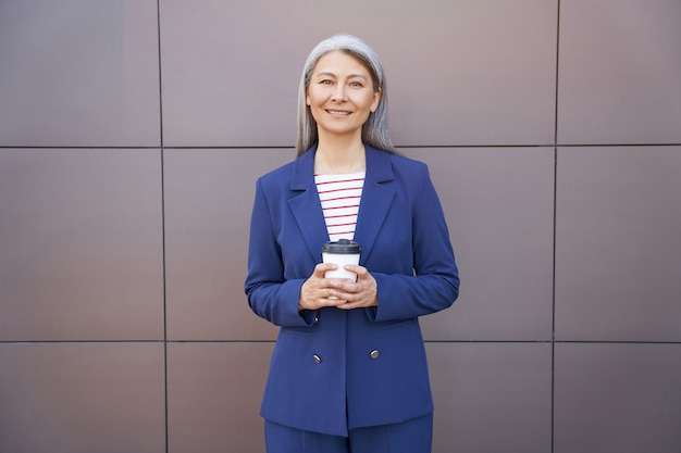 Retrato de una mujer de negocios madura hermosa feliz con anteojos y traje clásico sosteniendo la taza