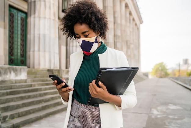 Retrato de mujer de negocios con máscara protectora y usando su teléfono móvil