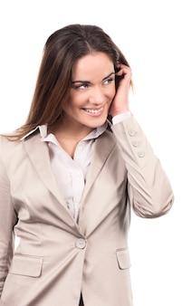 Retrato de mujer de negocios modelo con la mano en el cabello sobre fondo blanco.