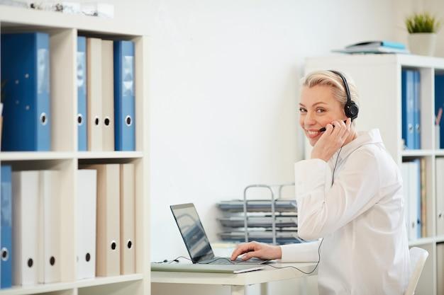 Retrato de mujer de negocios moderna usando auriculares y sonriendo mientras trabaja desde casa