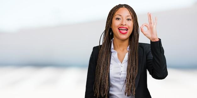 Retrato de una mujer de negocios negra joven alegre y confiada que hace el gesto aceptable, emocionado y gritando, concepto de aprobación y éxito