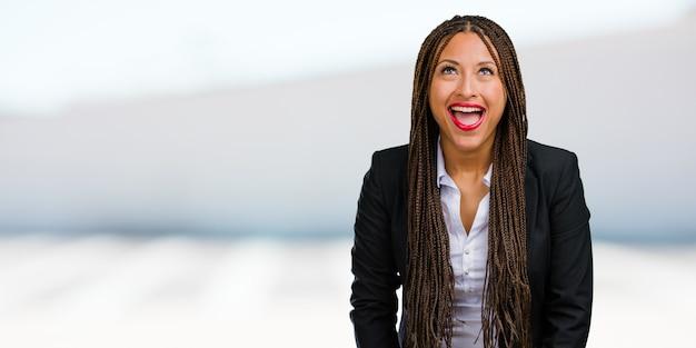 Retrato de una mujer de negocios negra joven que mira para arriba, pensando en algo divertido y teniendo