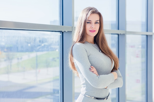 Retrato de una mujer de negocios en una oficina sobre un fondo de grandes ventanales