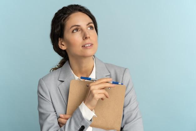 Retrato de mujer de negocios piensa mantener papeles y bolígrafo mirar pensativo a un lado aislado sobre fondo azul.