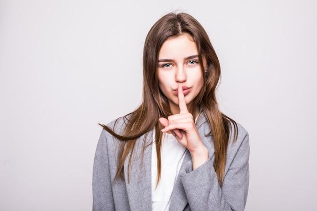 Retrato de una mujer de negocios con señal de silencio sobre fondo blanco.