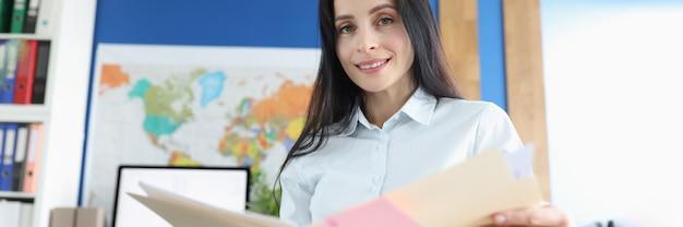 Retrato de mujer de negocios sentada en su escritorio y estudiando documentos financieros