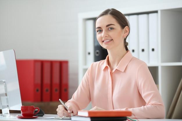 Retrato de mujer de negocios. él está sentado en una oficina a la mesa y mira a la cámara y sostiene un bolígrafo en la mano.