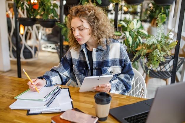 Retrato de mujer de negocios seria con taza de café, hacer bolsas durante el desayuno en el café