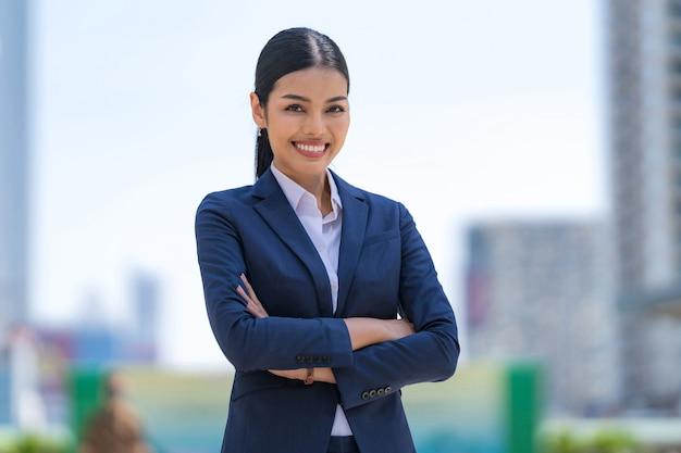 Retrato de mujer de negocios sonriente con los brazos cruzados mientras está de pie frente a modernos edificios de oficinas