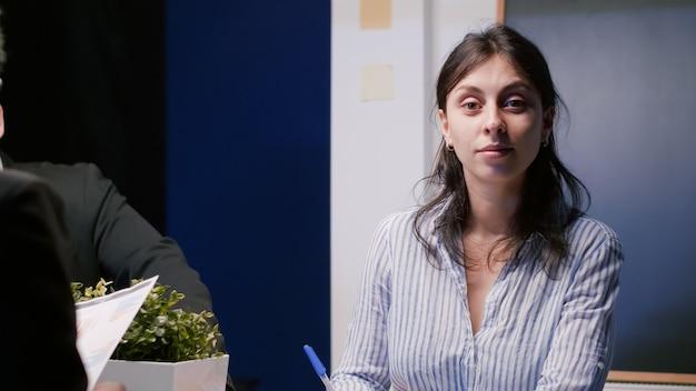 Retrato de mujer de negocios sonriente mirando a la cámara mientras está sentado en la mesa de conferencias