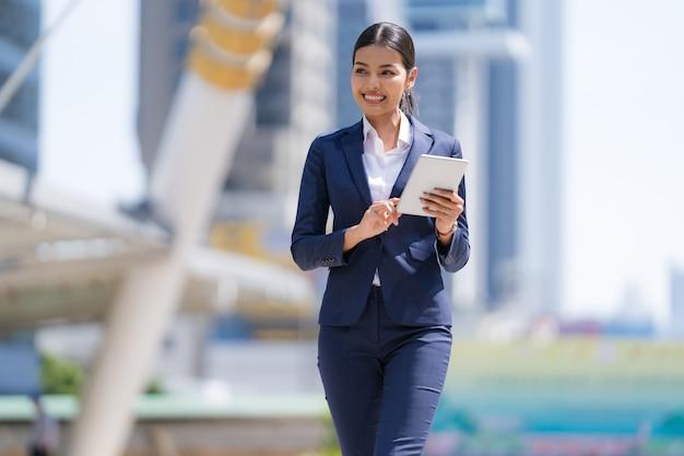 Retrato de mujer de negocios sonriente sosteniendo una tableta digital caminando frente a edificios de oficinas modernos
