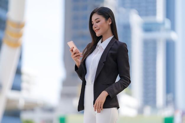 Retrato de mujer de negocios sonriente sosteniendo un teléfono de pie frente a modernos edificios de oficinas