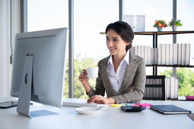 Retrato de mujer de negocios con taza de café en la oficina moderna