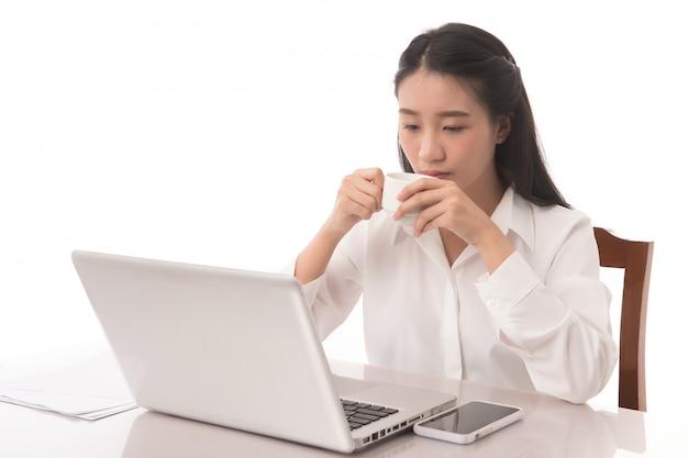 Retrato de mujer de negocios trabajando en su computadora portátil y tomando café en su oficina