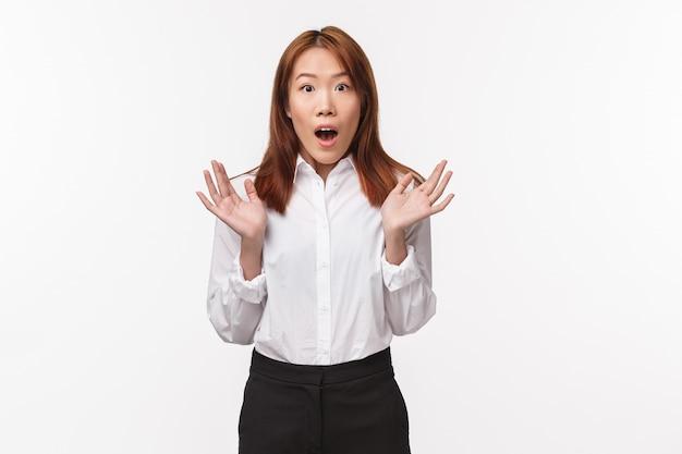 Retrato de una mujer de oficina asiática sorprendida y asombrada que jadea y mira fijamente la cámara sorprendida, levanta las manos asombradas cotilleando sobre algo asombroso, escucha noticias relacionadas,