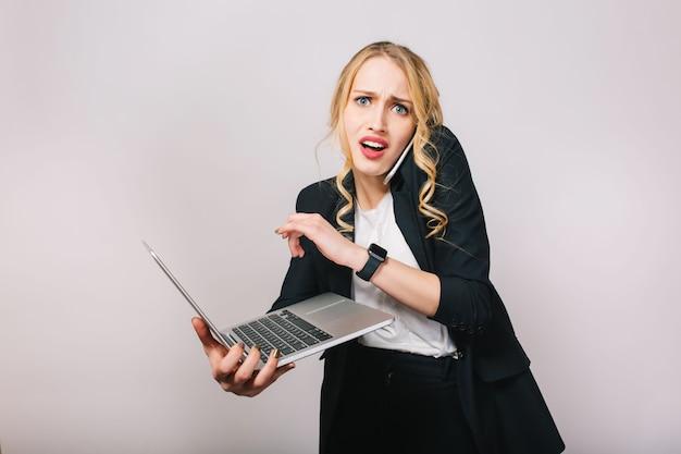 Retrato de mujer de oficina bastante rubia moderna en camisa blanca y chaqueta negra trabajando con ordenador portátil, hablando por teléfono. asombrado, llegar tarde, molesto, reuniones, expresar emociones verdaderas