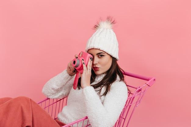 Retrato de mujer de ojos marrones con sombrero blanco y suéter tomando una foto en instax mientras está sentado en el carrito del supermercado en la pared rosa.
