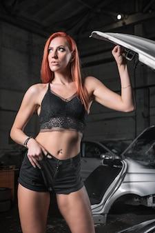 Retrato de mujer en pantalones cortos de jeans y top posando junto a un coche en el garaje, en coche viejo de fondo.