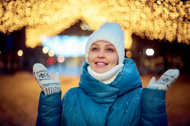 Retrato de una mujer en un parque de invierno en la noche, decoraciones de navidad, turismo y viajes.