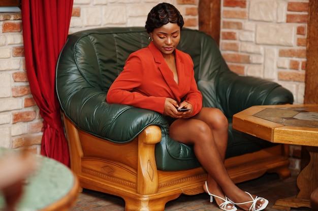 Retrato de mujer con peinado retro, sentada en un sofá con teléfono móvil