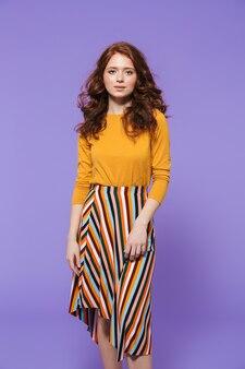 Retrato de una mujer pelirroja bastante joven de pie sobre violeta, posando, gesticulando