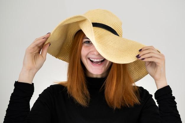 Retrato de mujer pelirroja divertida en bolsa de sombrero de paja amarilla.