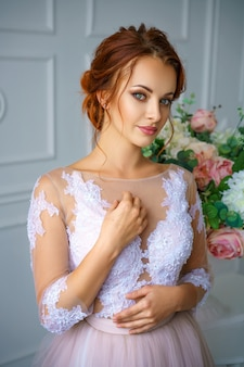 Retrato de una mujer pelirroja hermosa joven en un vestido delicado hermoso.