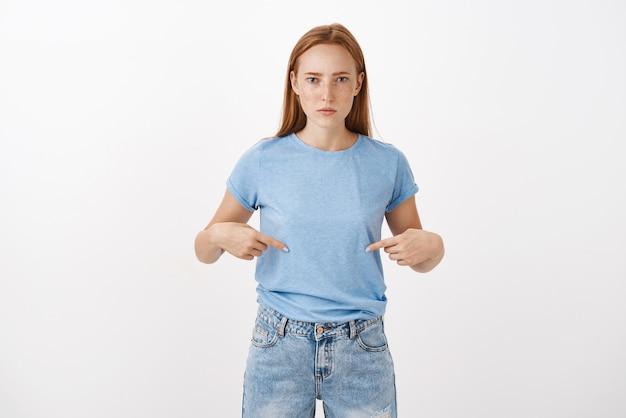 Retrato de mujer pelirroja intensa y disgustada seria mirando impasible apuntando al vientre con los dedos índices