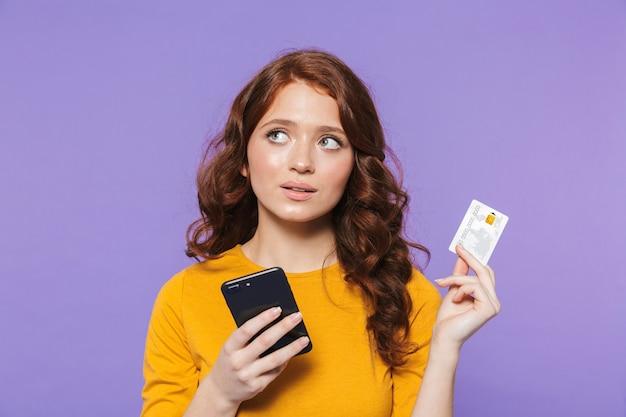 Retrato de una mujer pelirroja joven bastante alegre de pie sobre violeta, a través de teléfono móvil, mostrando la tarjeta de crédito