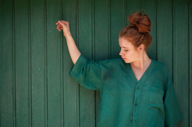 Retrato de mujer pelirroja sobre fondo verde