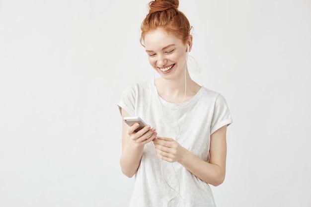 Retrato de mujer pelirroja sonriendo mensajes y escuchando streaming de música en auriculares con cable en la pared blanca.