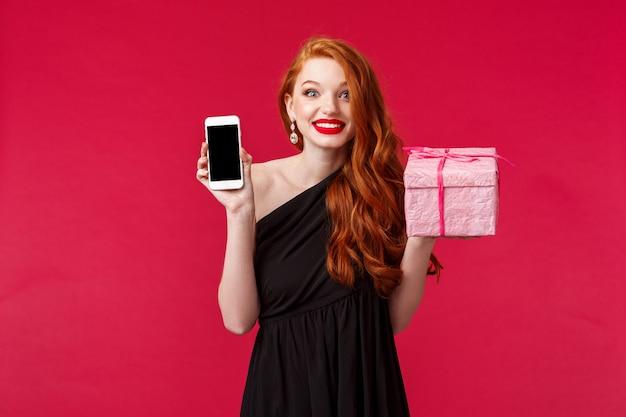 Retrato de una mujer pelirroja sonriente, emocionada y divertida, preguntada, no se expandió, recibió el regalo tan rápido, mostrando la aplicación de teléfono móvil, la aplicación de entrega en línea, sostenga el presente rosa sobre la pared roja