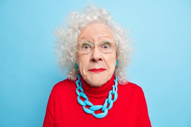 Retrato de mujer de pelo gris conmocionada mira con incredulidad