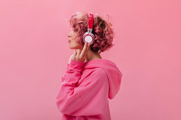 Retrato de mujer de pelo rosa rizado en enormes auriculares blancos