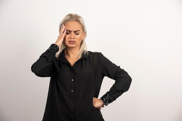 Retrato de mujer pensativa en camisa negra posando sobre fondo blanco. foto de alta calidad