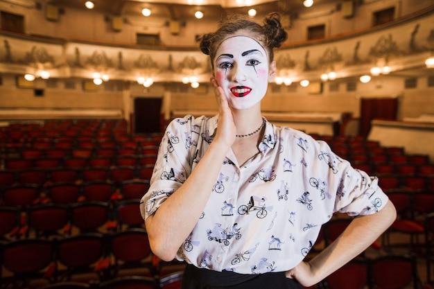 Retrato de mujer pensativa mime de pie en un auditorio