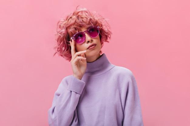 Retrato de mujer pensativa rizada de pelo rosa en suéter púrpura y gafas de sol fucsia posando en la pared aislada
