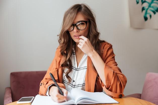 Retrato de una mujer pensativa tomando notas