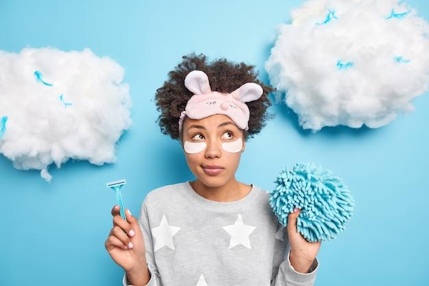 Retrato de mujer pensativa usa pijama sostiene navaja y esponja de baño concentrada a un lado tiene procedimientos de higiene diaria y tratamientos de belleza usa pijama con venda en la frente