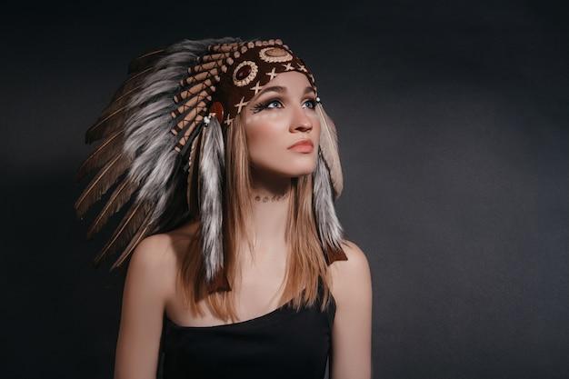 Retrato mujer perfecta en el atuendo de indios americanos en el humo en gris