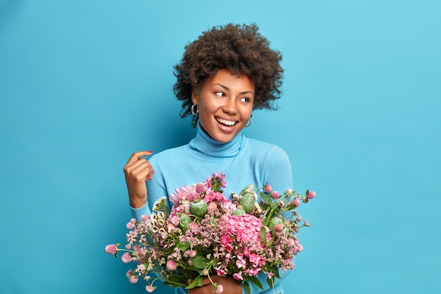 Retrato de mujer de piel oscura con cabello rizado mira con alegría lejos sostiene hermosas poses bouqet contra el fondo azul.