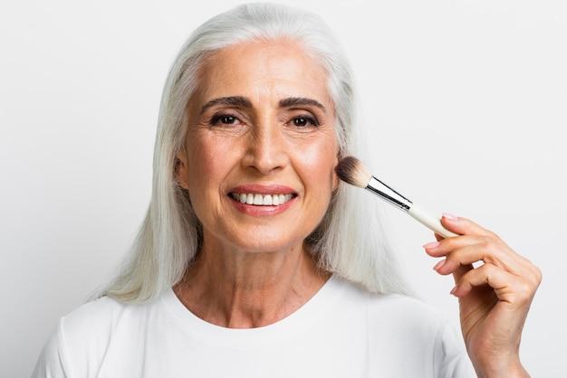 Retrato de mujer con pincel de maquillaje