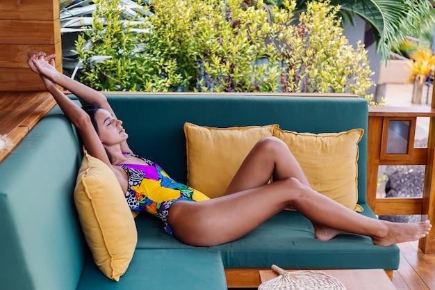 Retrato de mujer positiva delgada bastante en forma descansando con almohada en casa en el sofá de verano al aire libre, disfrutando del tiempo solo