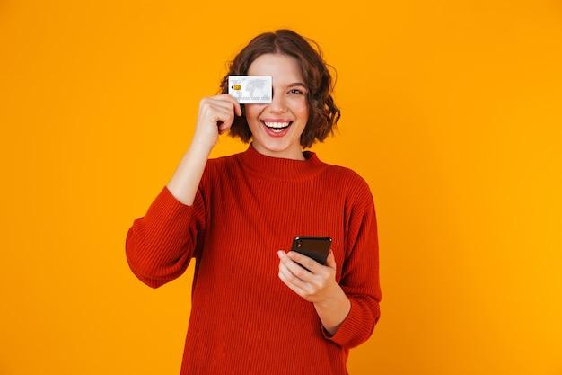 Retrato de mujer positiva vistiendo suéter con teléfono celular y tarjeta de crédito mientras está de pie aislado en amarillo