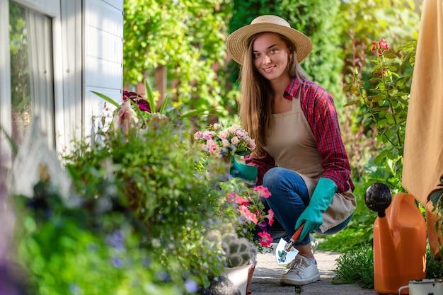 El retrato de la mujer que cultiva un huerto feliz en guantes, sombrero y delantal planta la flor de la petunia en la cama de flor en jardín. jardinería y floricultura. cuidado de la flor