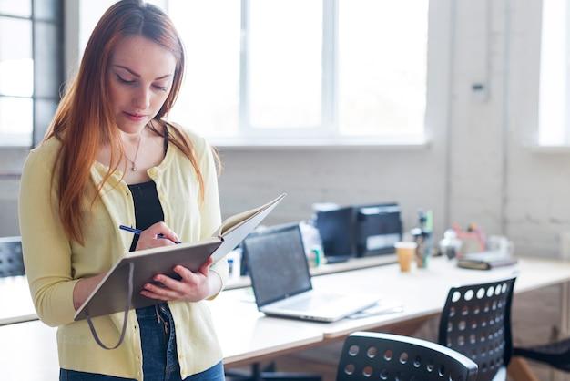 Retrato de la mujer que hace algunas notas en libreta en el lugar de trabajo
