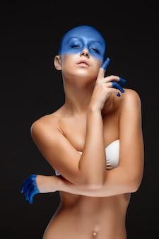 Retrato de una mujer que posa cubierta con pintura azul