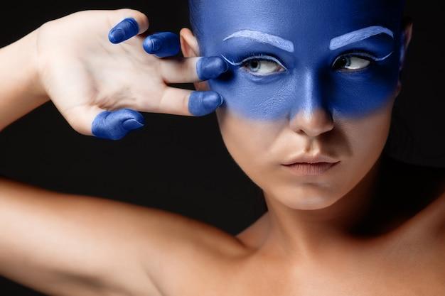 Retrato de una mujer que está posando cubierta con pintura azul