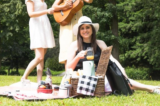 Retrato de la mujer que sostiene el tarro del jugo con sus amigos en comida campestre