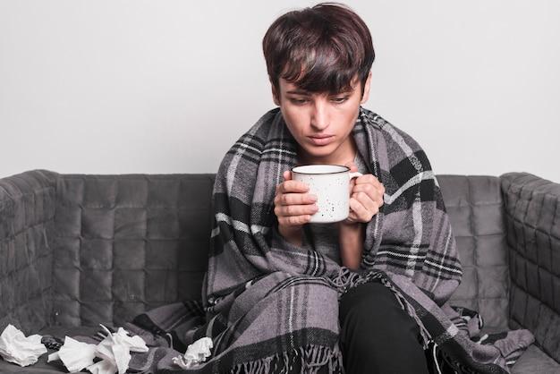 Retrato de la mujer que sufre de frío sosteniendo la taza de café